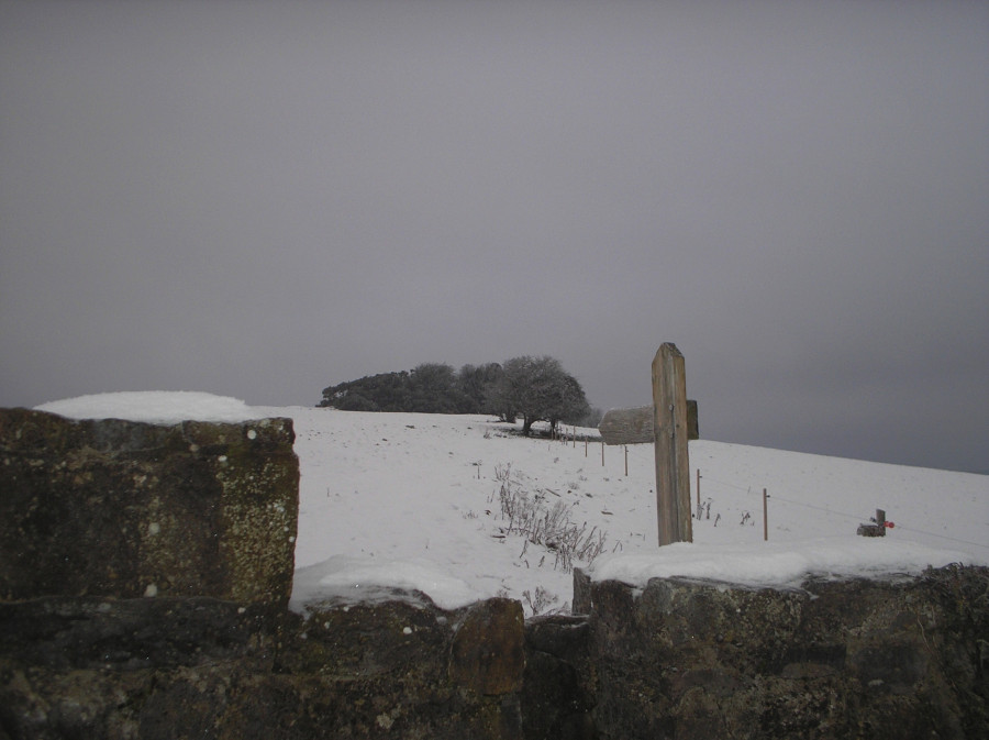 Looking over the stile toward the cairn in the snow